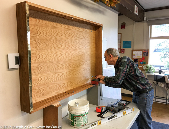 Terry attaching the cabinet to the wall