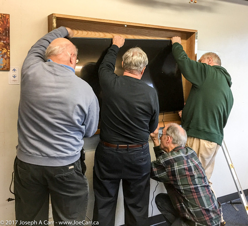 Reg, Dave, Terry and Les lift the TV up to the mount